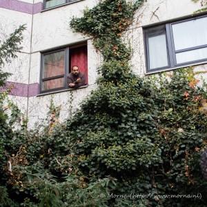 Een man kijkt uit het raam in een migrantenwijk in Berlijn