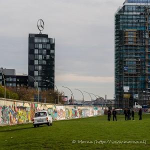 Een auto uit het DDR-tijdperk voor de Berlijnse muur, met op de achtergrond een nieuw gebouw van Mercedes.