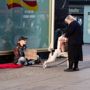 """Een vrouw geeft kleingeld aan een meisje met een hond dat bedelt met het bordje """"For Beer and Weed"""""""
