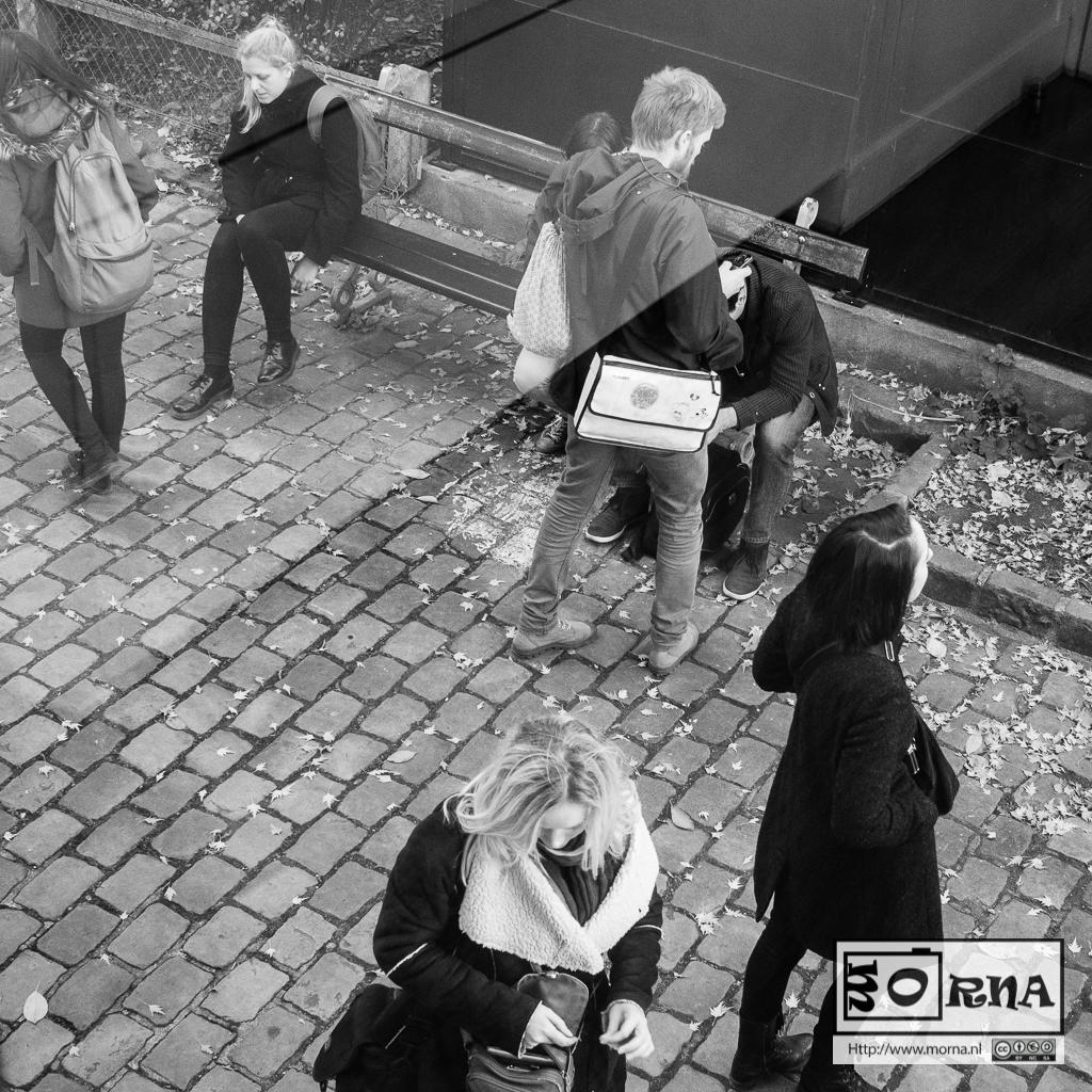 Een groep mensen verspreid over een straat, op een bankje zit iemand, er staat een man recht voor, enkele vrouwen lopen in de buurt.